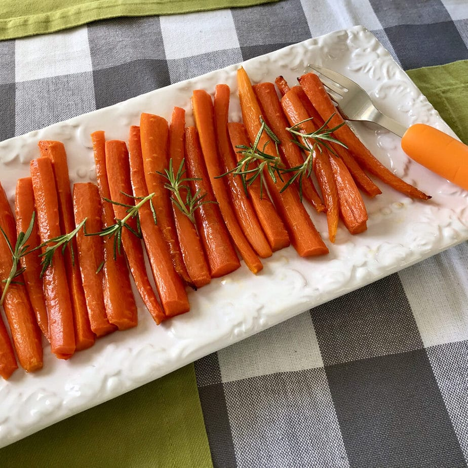 A rectangular plate arranged with maple balsamic roasted carrots.