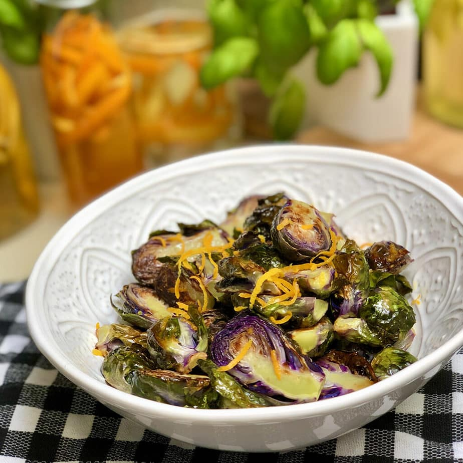 A white bowl filled with roasted purple Brussels sprouts topped with balsamic orange sauce and zest.