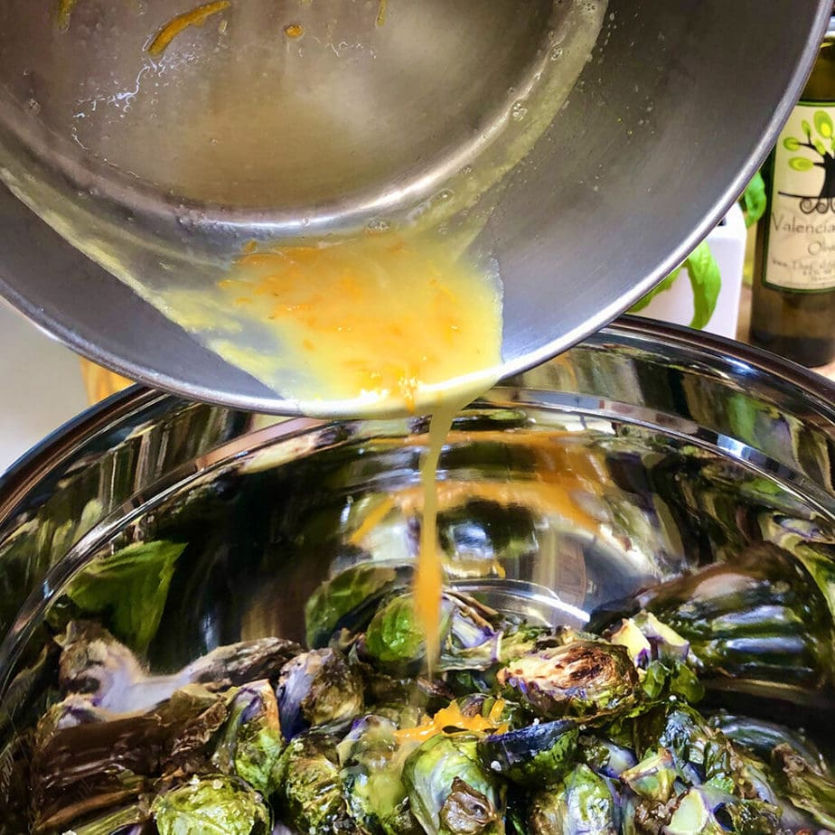 pouring orange sauce over brussels sprouts