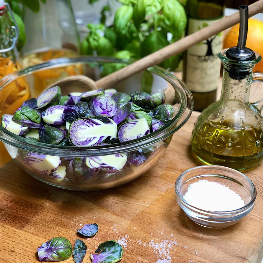 Purple Brussels sprouts in a clear bowl with salt & olive oil.