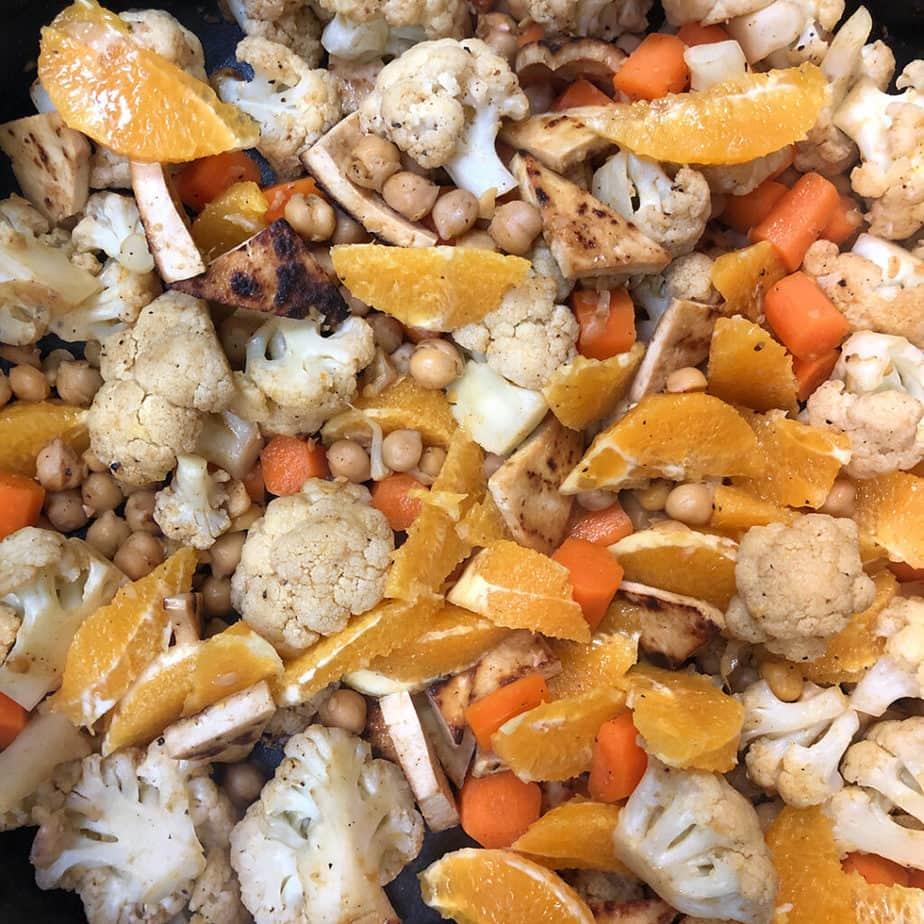 tofu, cauliflower, carrots, chickpeas, orange slices in skillet