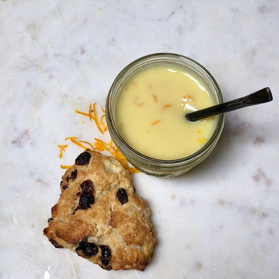 overhead shot of vegan orange curd in jar and scone