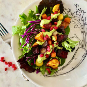 roasted carrots and beets on a bed of romaine and red cabbage, tooped with vegan avocado basil dressing