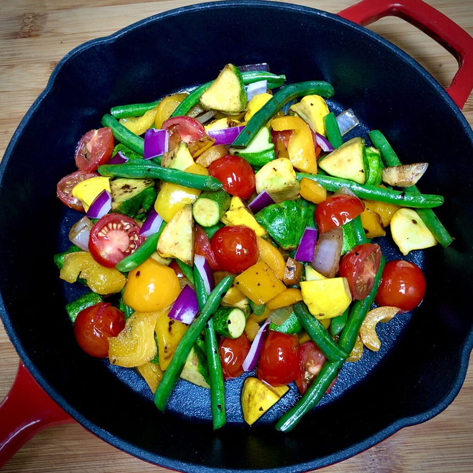 skillet with sautéed zucchini, yellow squash, summer squash, bell pepper, green beans, red onion and cherry tomatoes
