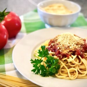 easy vegan parmesan cheese on top of a plate of spaghetti with marinara