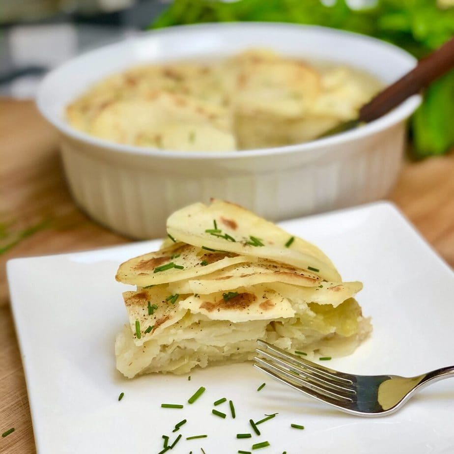 A serving of vegan scalloped potatoes with cabbage on a white plate.