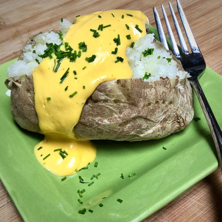 baked potato with easy vegan cheese sauce and chopped chives