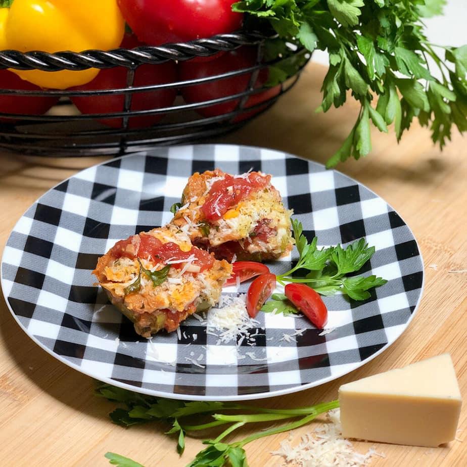 Vegan Zucchini Ravioli on a checkered plate, topped with marinara sauce and vegan parmesan