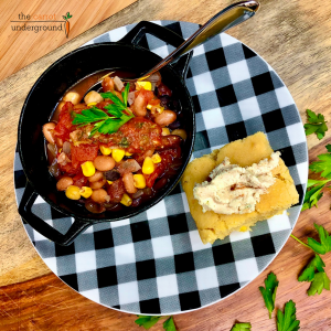 a cast iron bowl filled with vegan chili, sitting on a back and white gingham print plate with a slice of vegan cornbread.