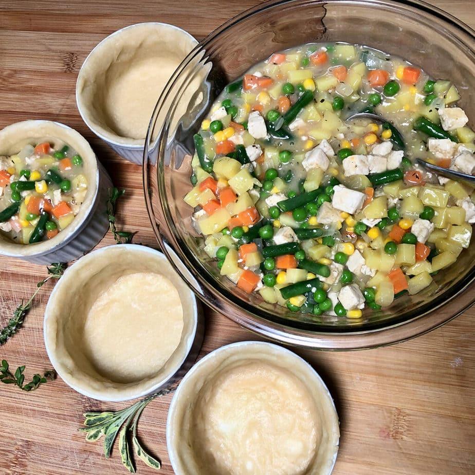 spooning vegan pot pie ingredients into pie shells