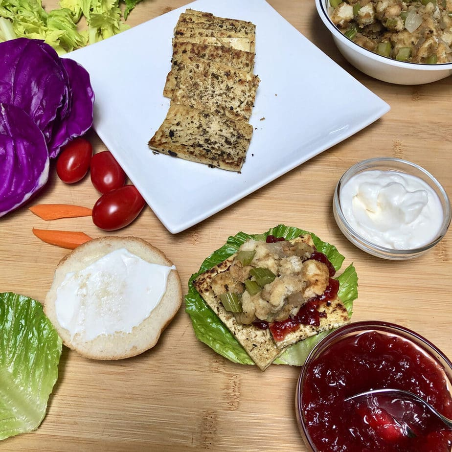 savory herbed tofu slices on plate with sandwich ingredients