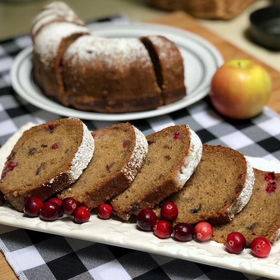 sliced vegan applesauce cake on plate with cranberries
