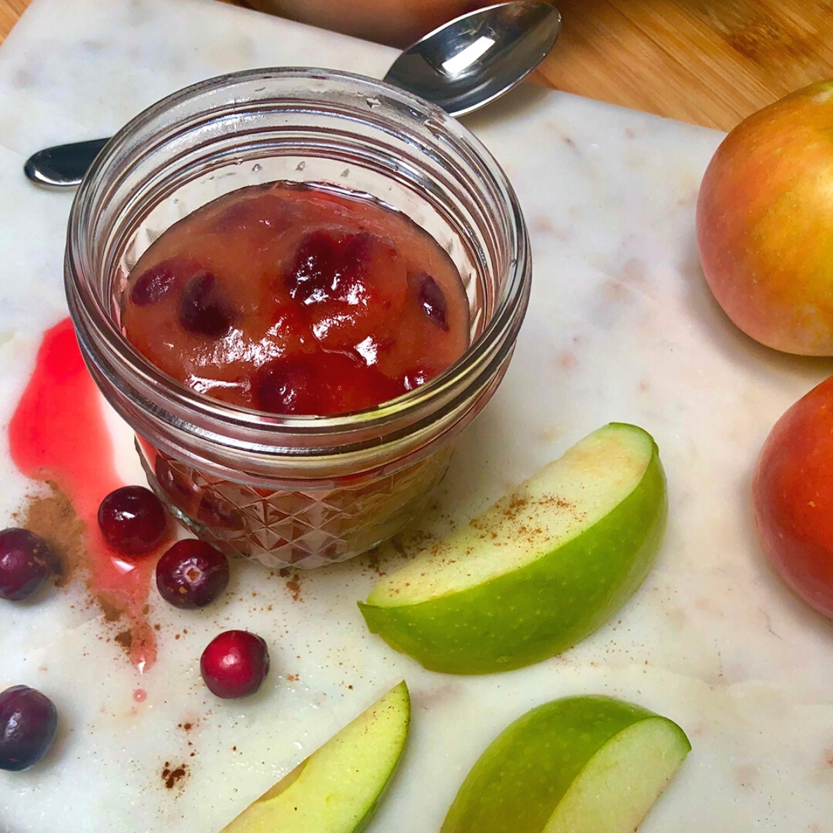 A mason jar with homemade cranberry applesauce on a marble block with apple slices and fresh cranberries scattered on top.