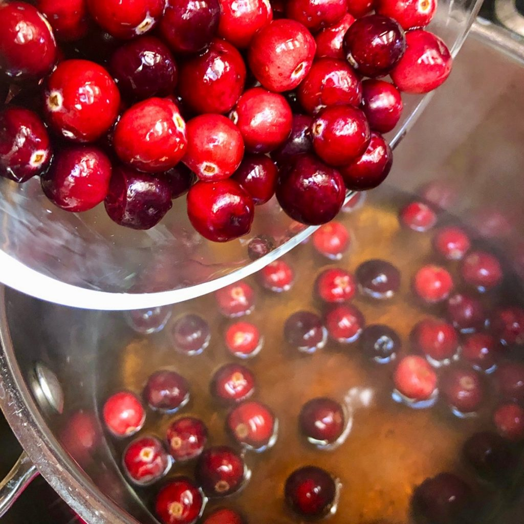 Adding fresh cranberries to pan with maple syrup.
