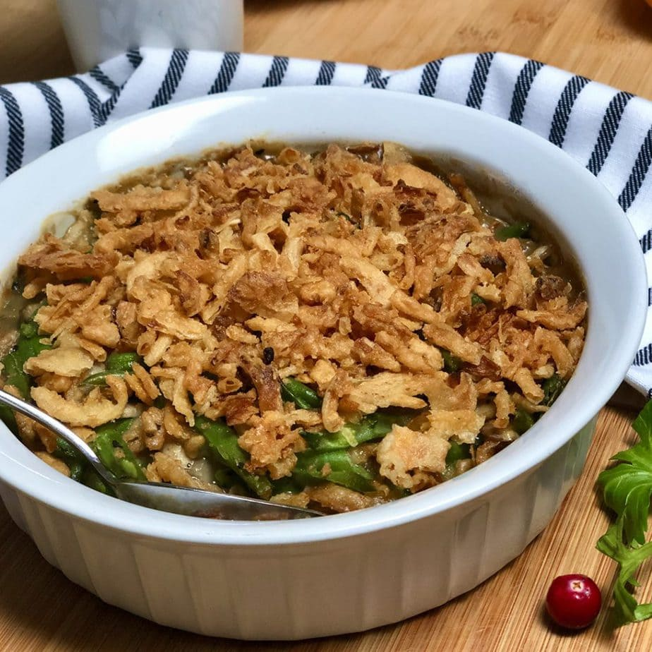 A white baking dish filled with vegan green bean casserole.