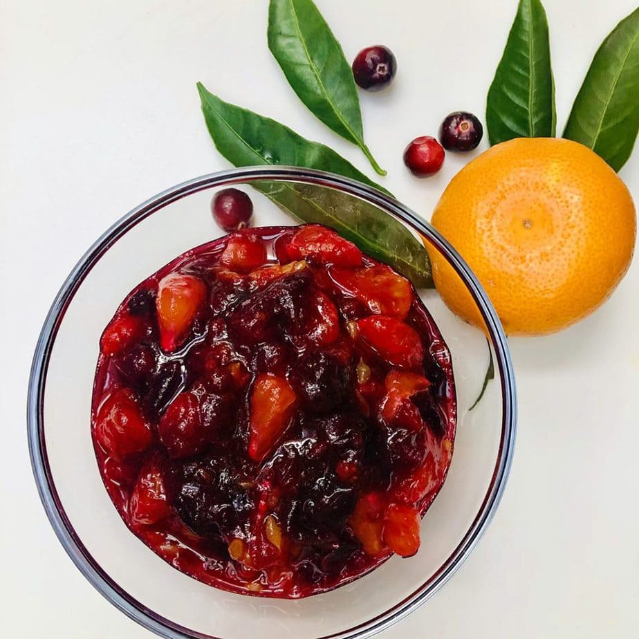 Homemade cranberry orange sauce in a glass bowl with a whole  tangerine on the side.
