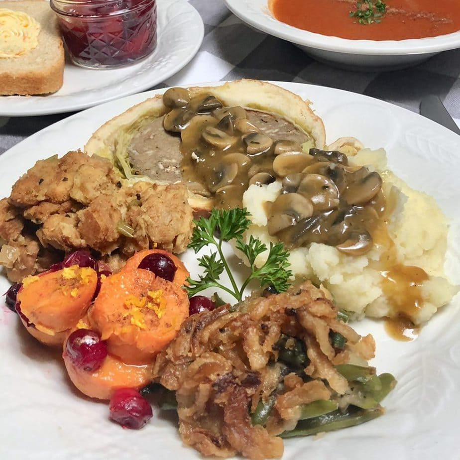 Vegan Thanksgiving dinner with mashed potatoes, yams, stuffing, green bean casserole and seitan loaf