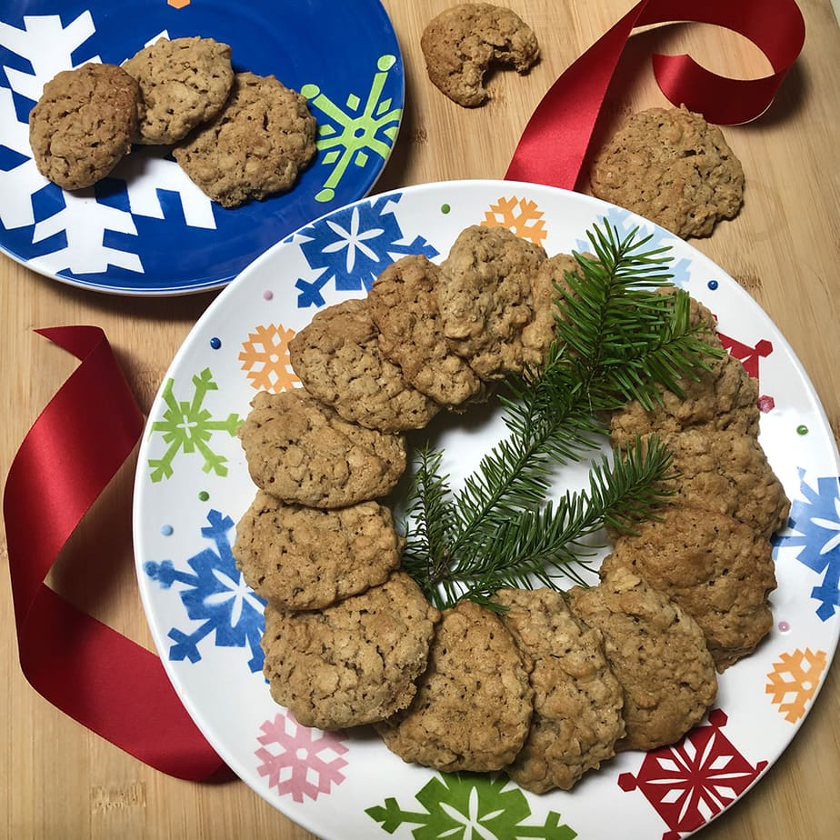 Simple vegan old fashioned oatmeal cookies arranged on a festive plate with red ribbon and pine sprig.