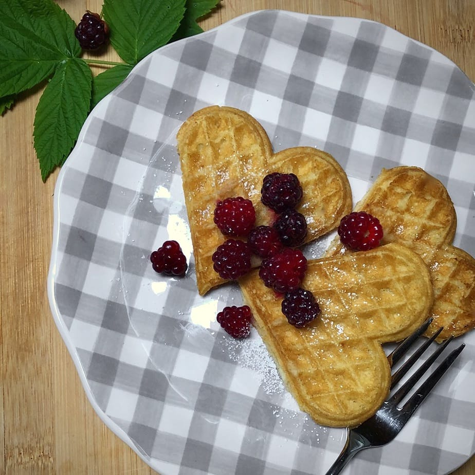 Easy vegan heart shape waffles on gingham plate with berries.