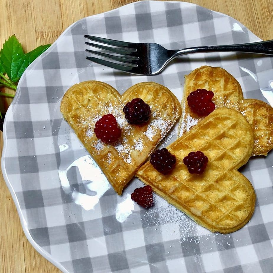 easy vegan heart shaped waffles with berries on gingham plate.