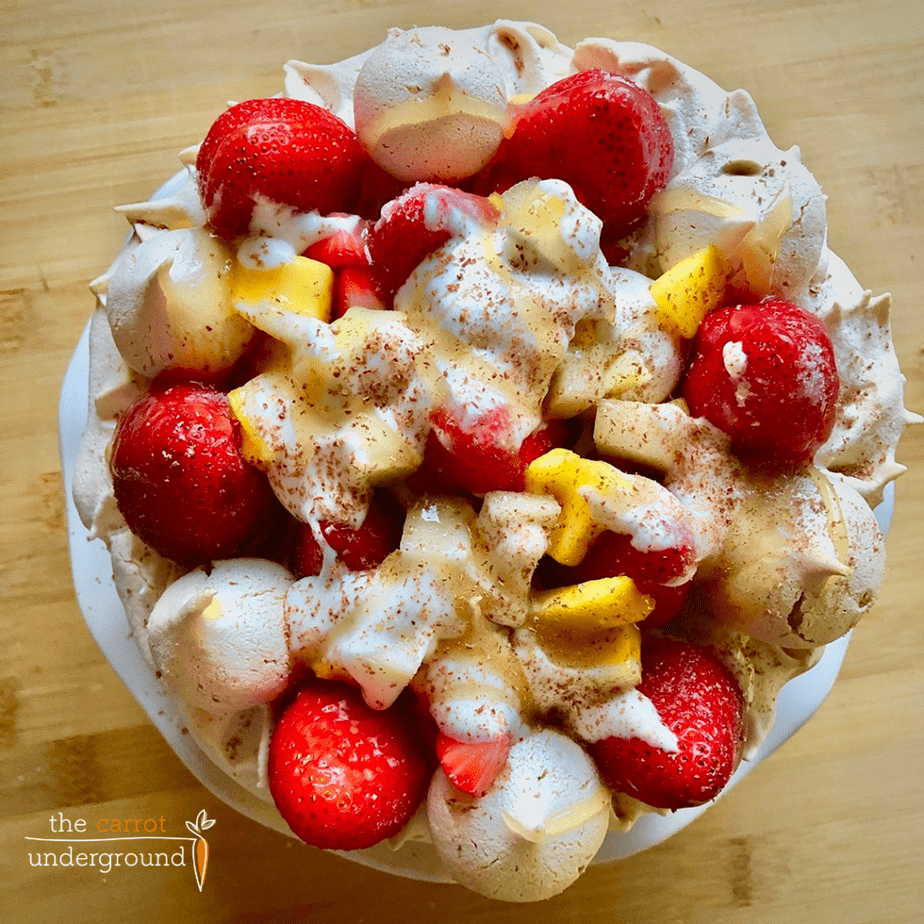 overhead view of a vegan pavlova made with vegan meringue layered and topped with fresh strawberries and mangoes