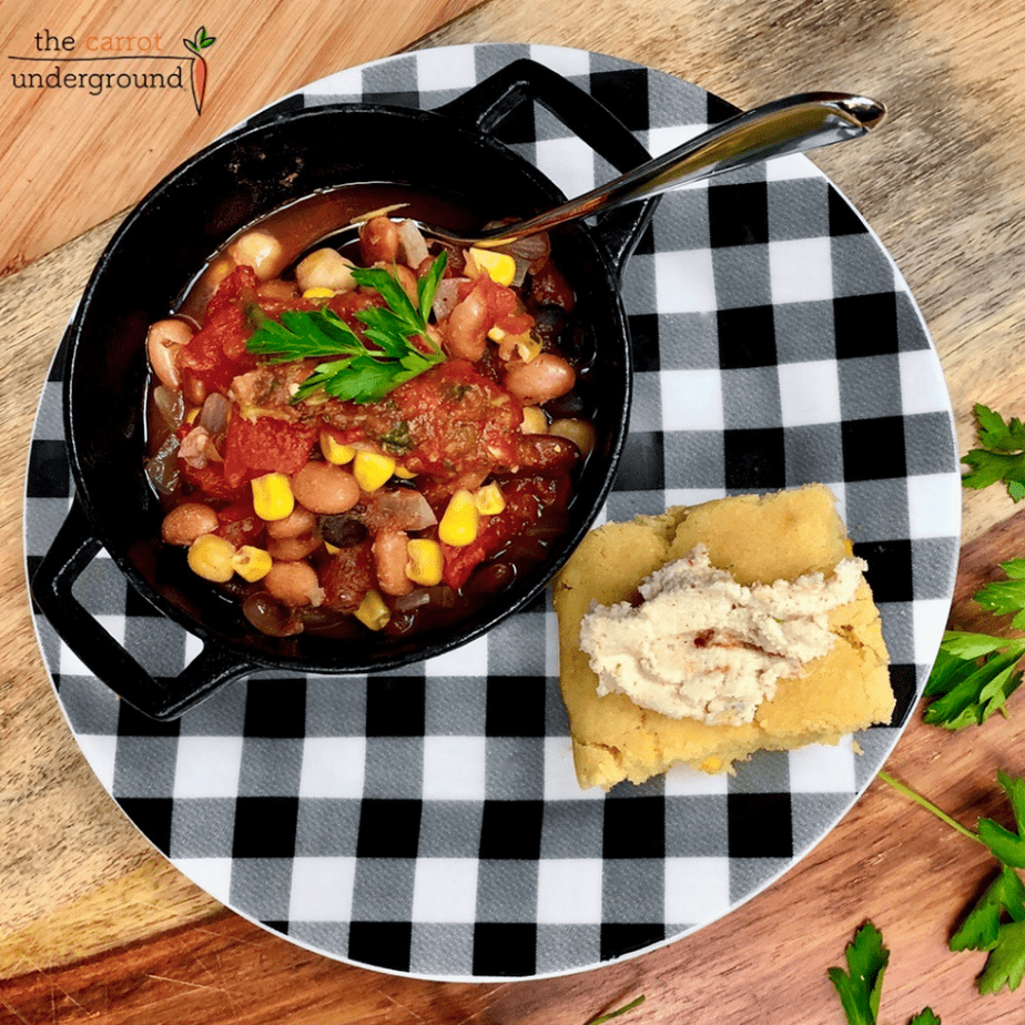 a bowl of vegan chili with a slice of homemade vegan cornbread on a checkered plate
