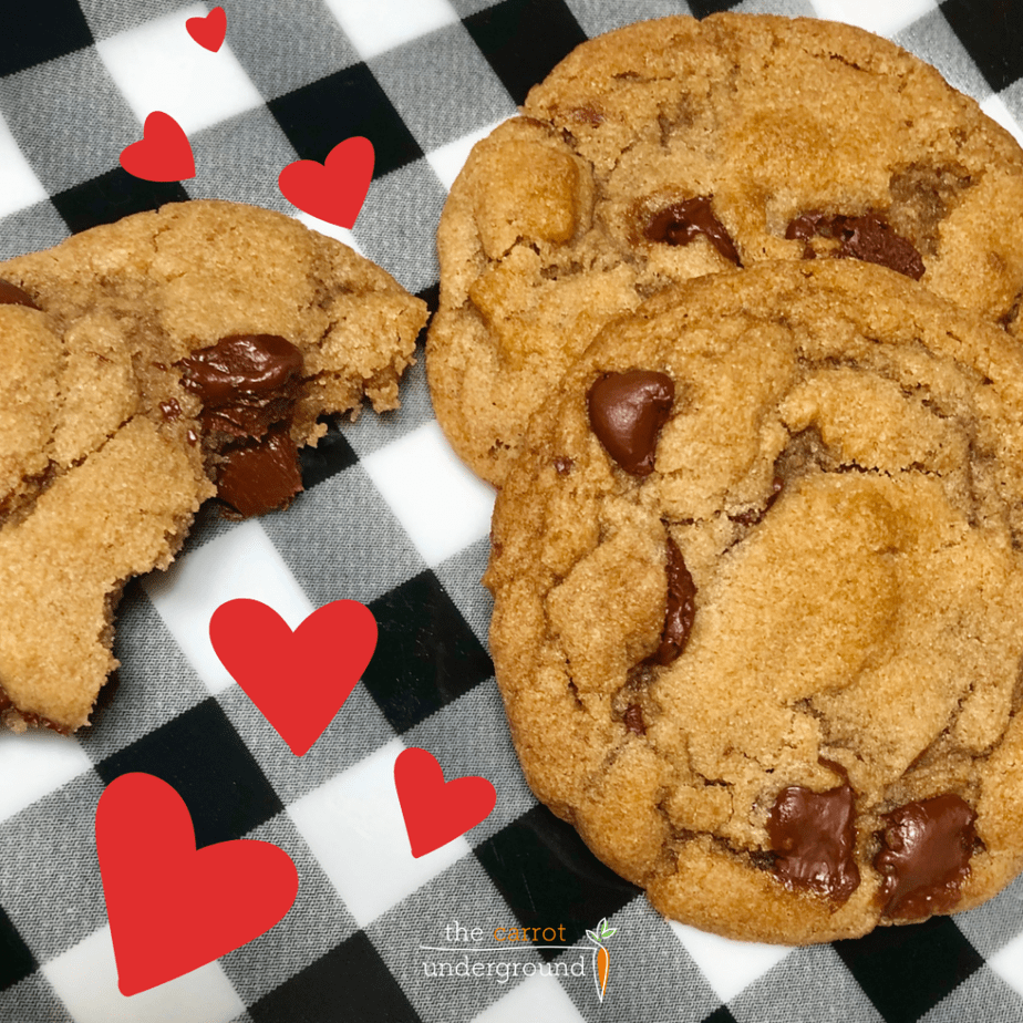 A black and white gingham print with vegan chocolate chip cookies and red heart graphics