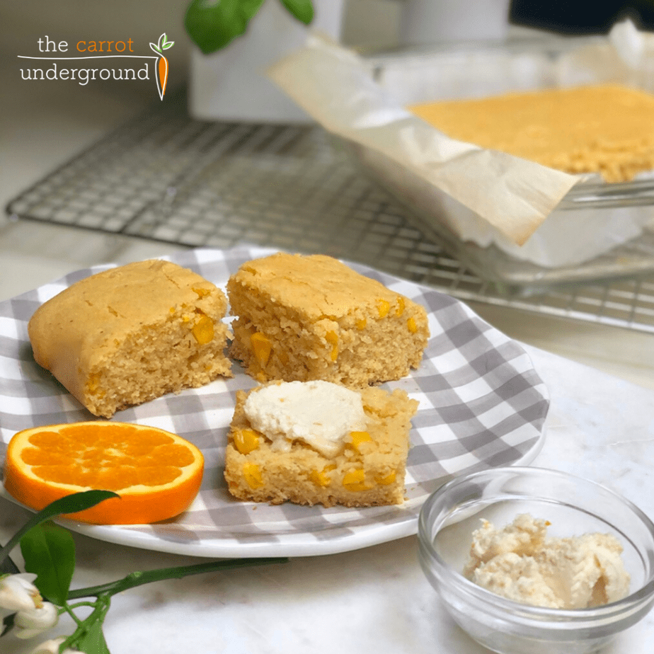 slices of homemade vegan cornbread on a checkered plate with orange slices and butter