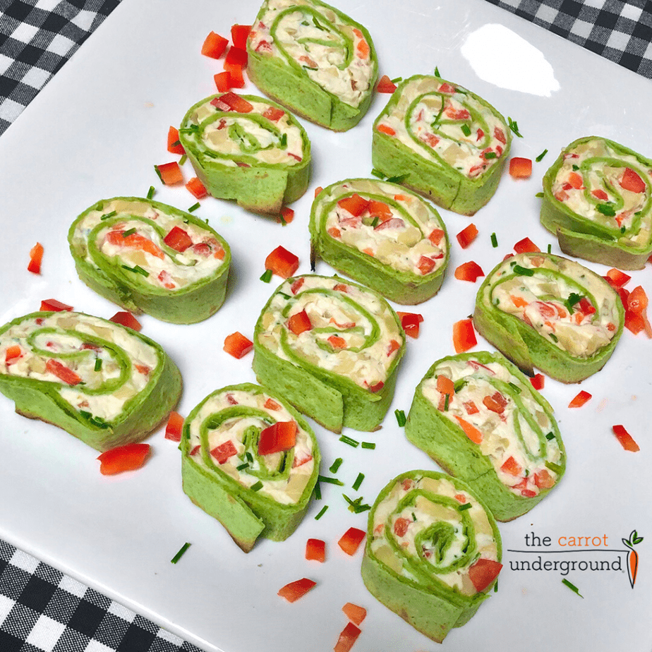 a platter of vegan fiesta pinwheels made with spinach tortillas filled with vegan cream cheese, olives, artichoke hearts & red bell pepper