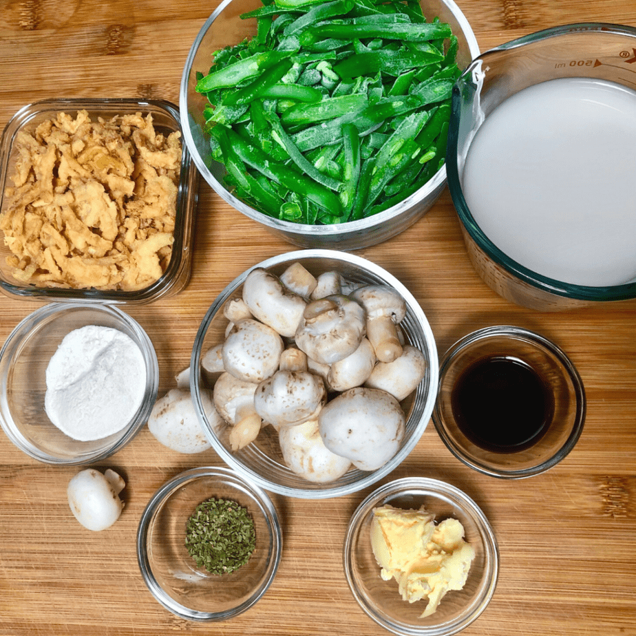 Ingredients for vegan green bean casserole including green beans, mushrooms, herbs, butter, soy sauce, onion rings