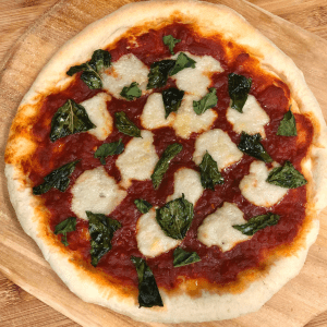 A Homemade Vegan Margherita Pizza on a wooden pizza paddle