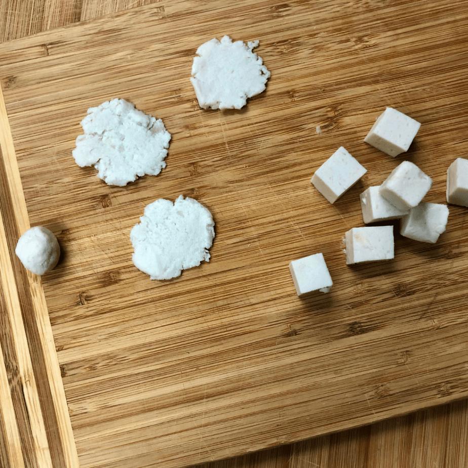 Flattened vegan mozzarella rounds on a cutting board.