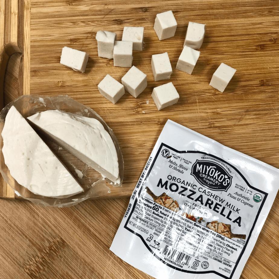 Cubes of Miyoko's vegan mozzarella on a cutting board.