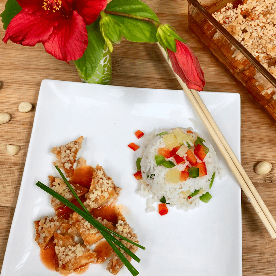 a square plate with triangles of sweet & sour tofu and steamed rice.