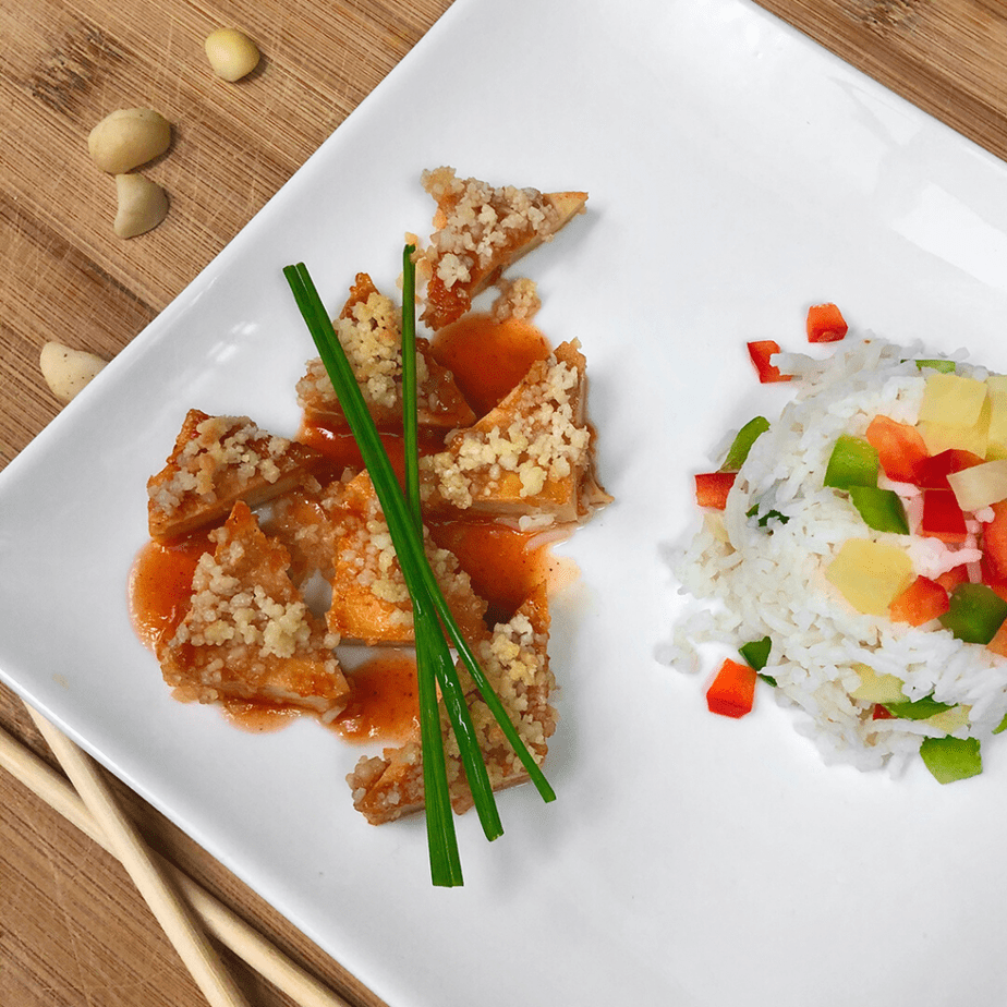 Triangles of vegan sweet & sour tofu and rice with chives on a plate.