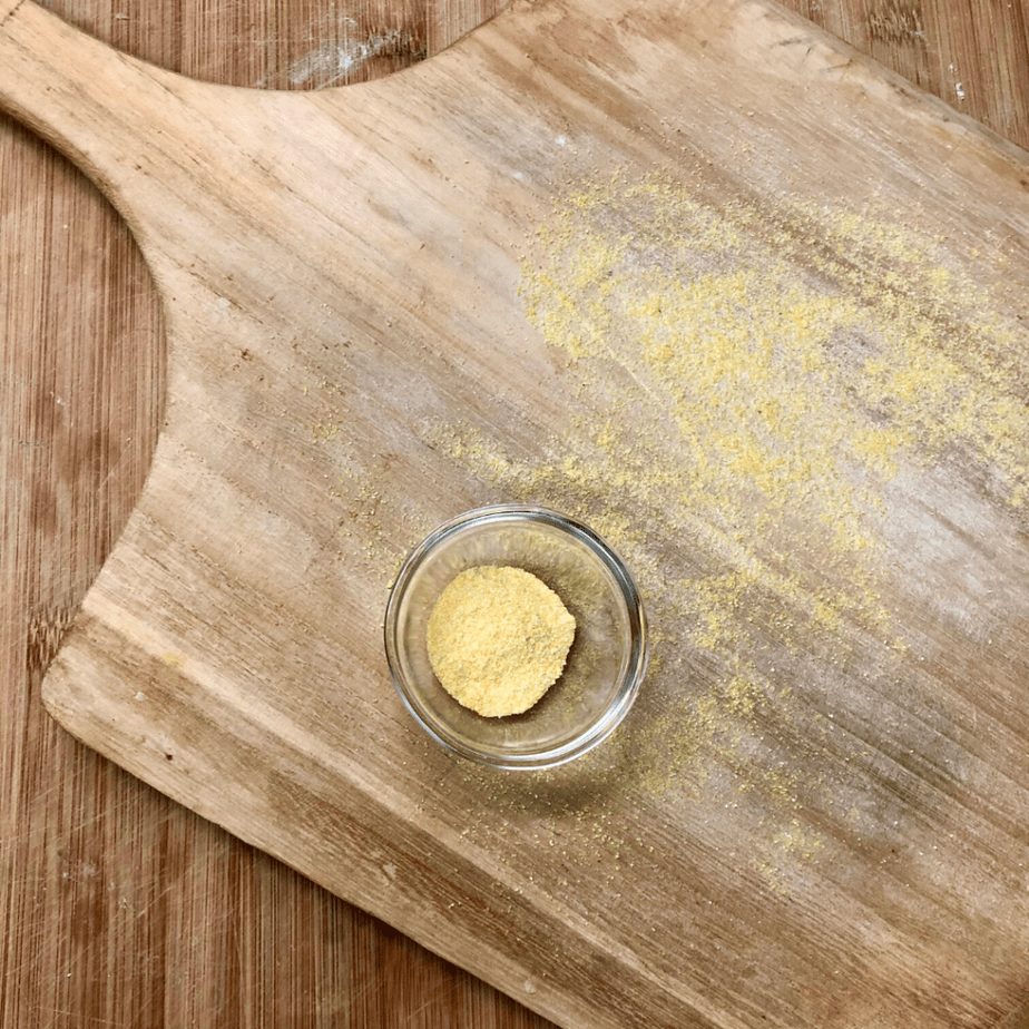 Pizza paddle dusted with cornmeal.