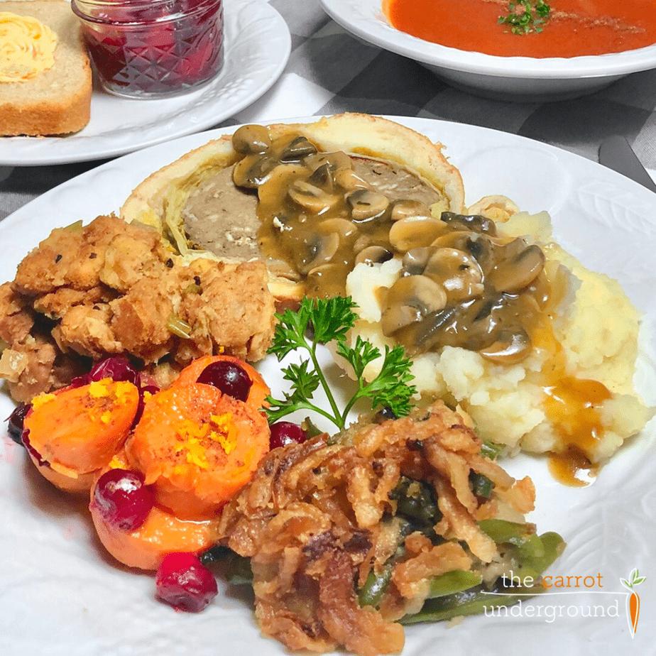 Dinner plate with vegan green bean casserole, cranberry maple yams, vegan stuffing, mashed potatoes & mushroom gravy and vegan mushroom wellington