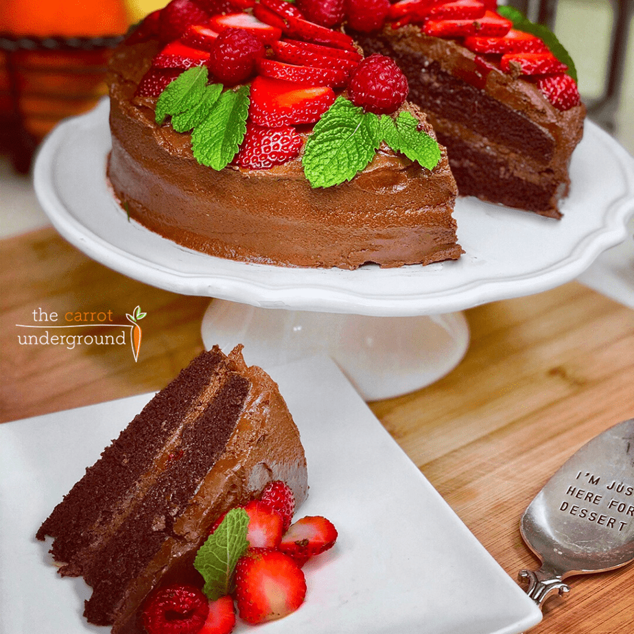 Vegan devil's food cake, decorated with sliced strawberries on a cake stand and a slice of cake, plated.