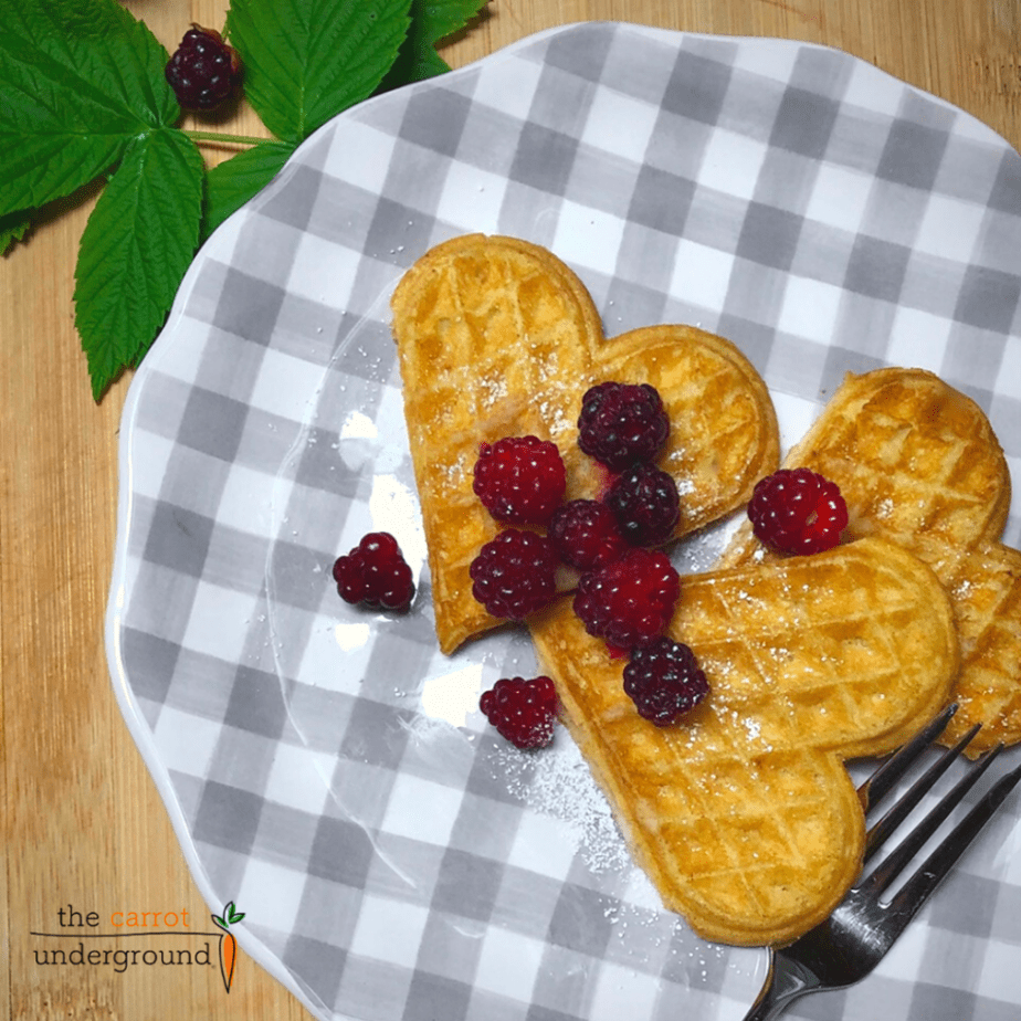 Heart shaped vegan waffles with berries on a gingham print plate.