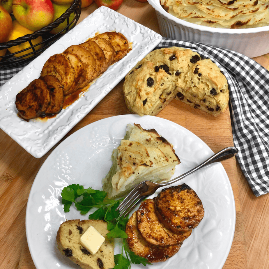 A variety of vegan Irish dishes on a wood  table, including scalloped potatoes and cabbage, Irish soda bread and sliced tofu roast.