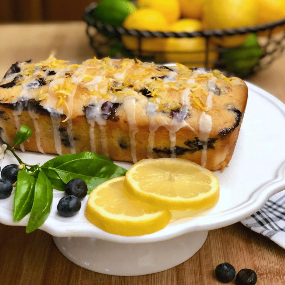 Simple Vegan Lemon Blueberry Bread on cakestand with lemon slices and fresh blueberries