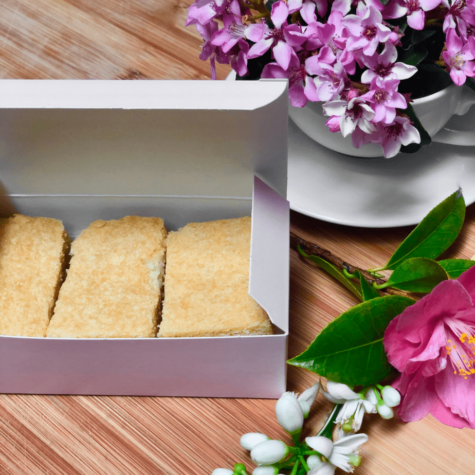 Ted Lasso inspired vegan shortbread in a pink box with fresh flowers on a table.
