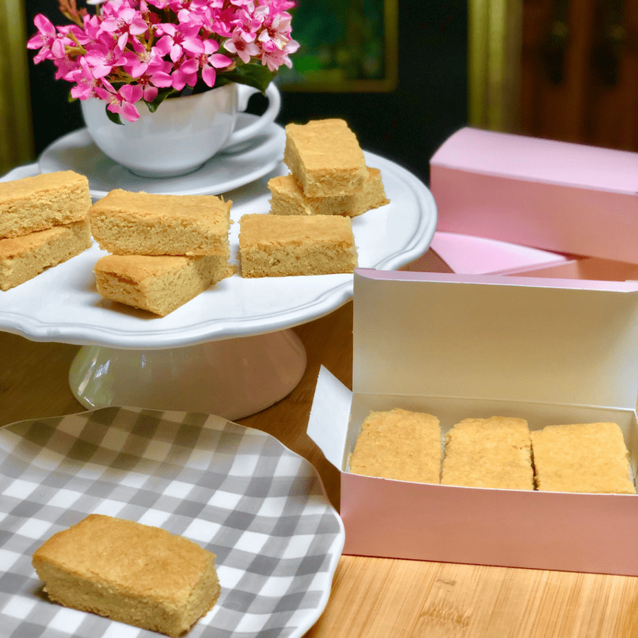 Vegan shortbread biscuits arranged on a cake plate and in pink pastry boxes.