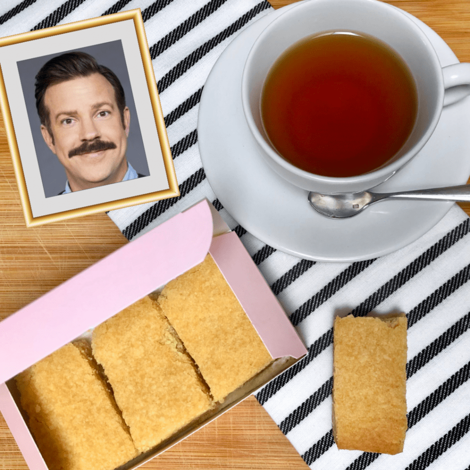 A pink box filled with vegan shortbread biscuits or cookies with a cup of tea and a framed image of the actor Jason Sudeikis as Ted Lasso.
