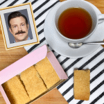 Overhead image of vegan shortbread biscuits in a pink box, a cup of tea and a photo of Jason Sudeikis as Ted Lasso in a frame on a striped tea towel.