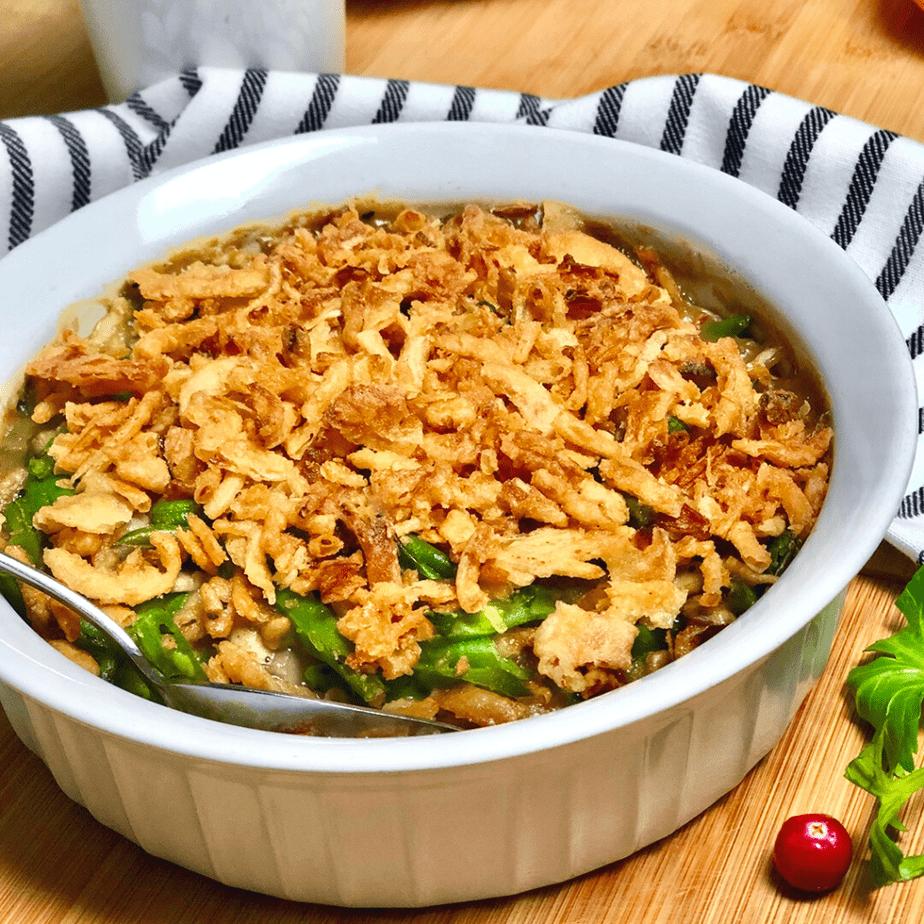 A round white baking dish with vegan green bean casserole