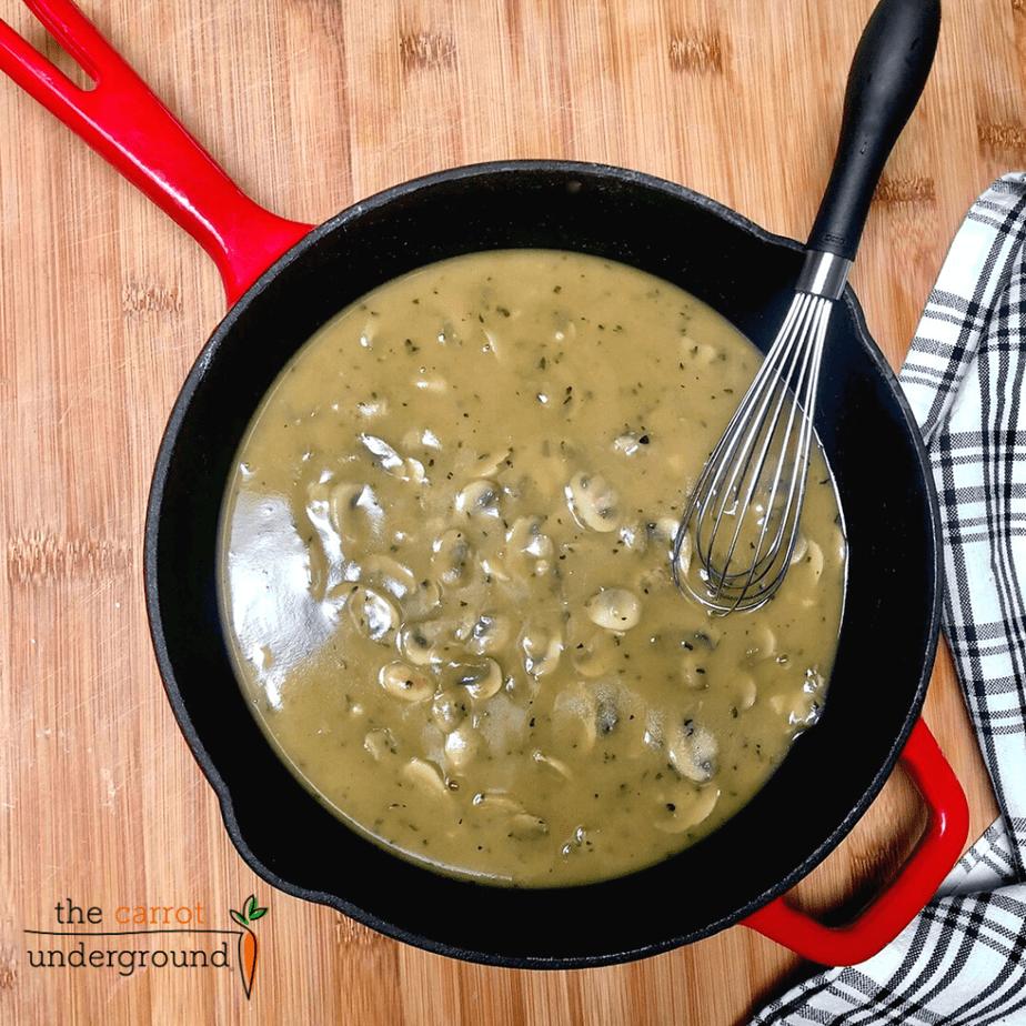 Vegan mushroom gravy in a skillet with a whisk.
