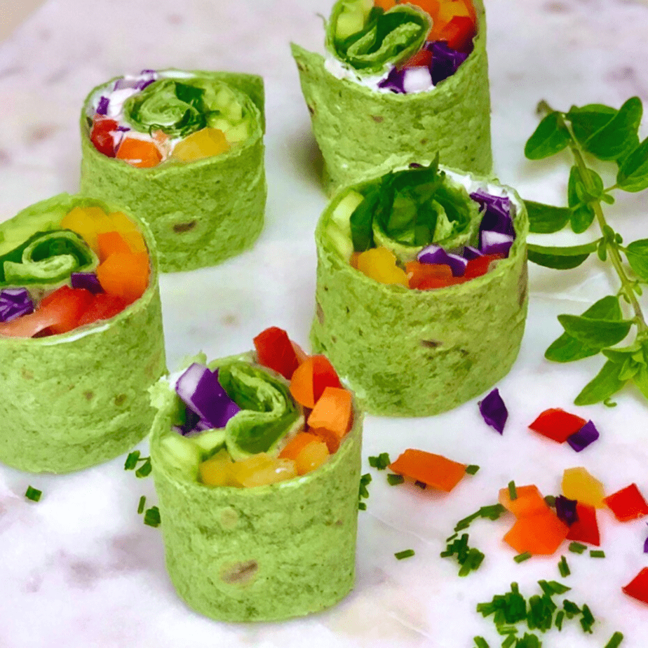 Vegan Rainbow wraps made with spinach tortillas rolled with vegan cream cheese and fresh veggies