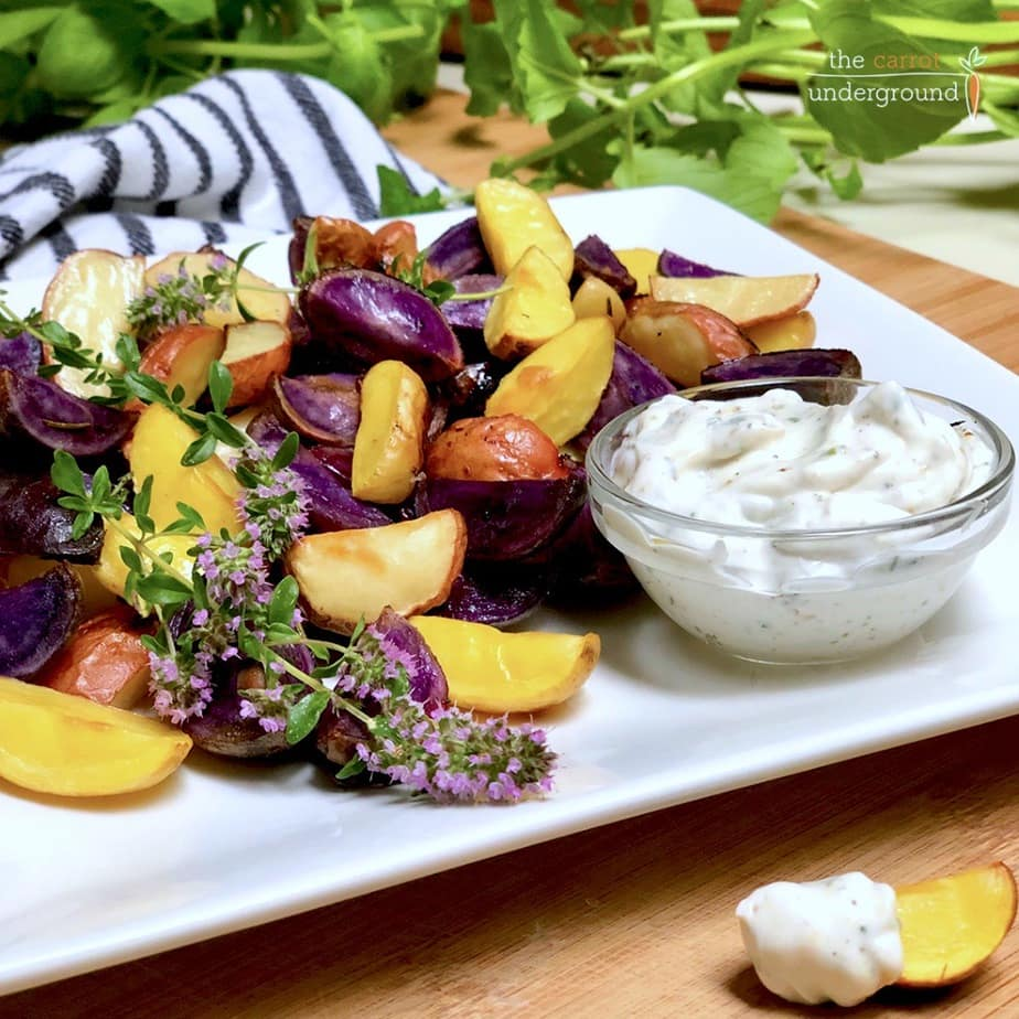 Plate with lemon roasted rainbow potatoes and a dish of vegan ranch dressing.
