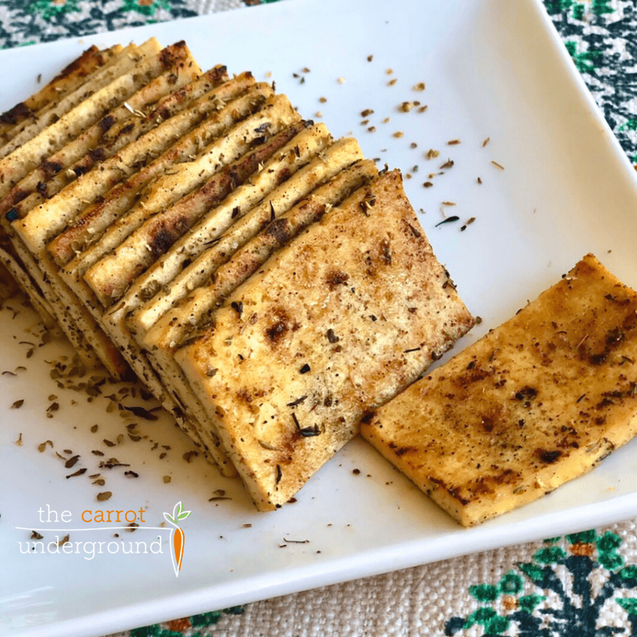 Slices of savory herbed tofu on a plate
